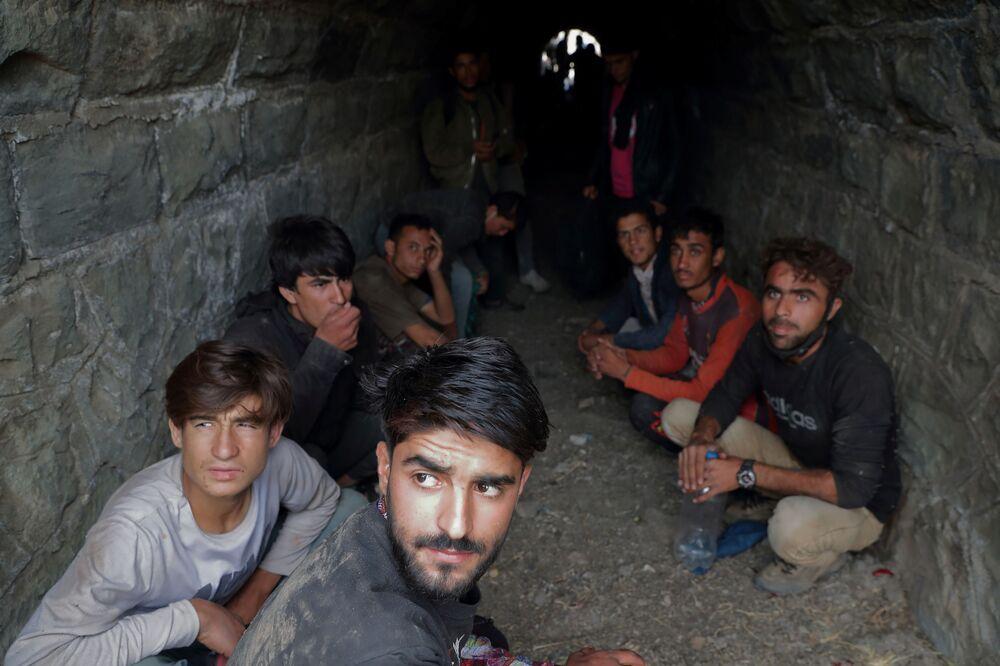جندي باكستاني يتحقق من وثائق الأشخاص الوافدين من المهاجرين الأفغان المختبئين من قوات الأمن في نفق تحت سكة القطار بعد عبورهم بشكل غير قانوني إلى تركيا من إيران، بالقرب من تاتفان في مقاطعة بدليس، تركيا، 23 أغسطس 2021