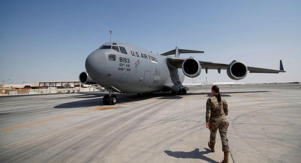 ضابط بالجيش الأمريكي تسير باتجاه طائرة تابعة للقوات الجوية الأمريكية في قاعدة العديد الجوية في الدوحة