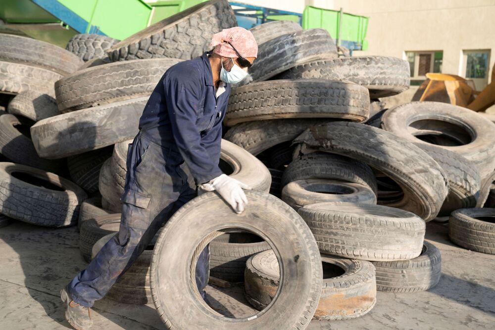 صورة لعامل في EPSCO Global General Trading وهو يستعد لإعادة تدوير إطار في مصنع إعادة تدوير الإطارات في منطقة السالمي، الكويت، 1 سبتمبر 2021