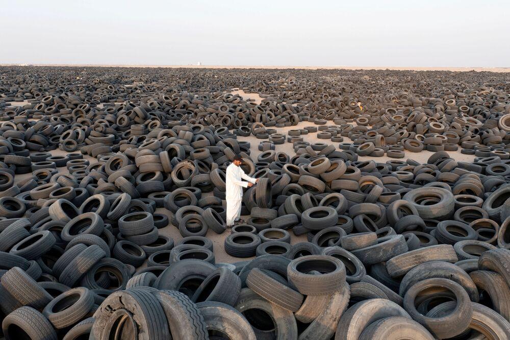 المقاول السوري، إبراهيم كمال، يقف وسط الإطارات التالفة المعدة لإعادة تدوير في منطقة السالمي، الكويت 4 سبتمبر 2021
