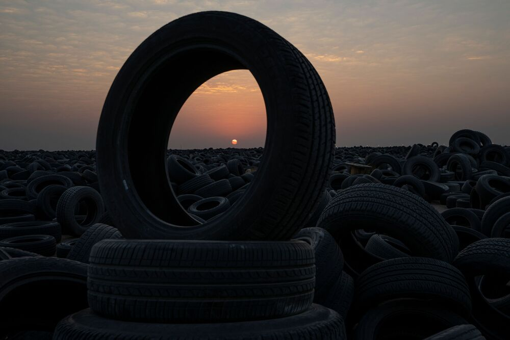 غروب الشمس على خلفية مقبرة للإطارات التالفة في منطقة السالمي، الكويت، 4 سبتمبر 2021