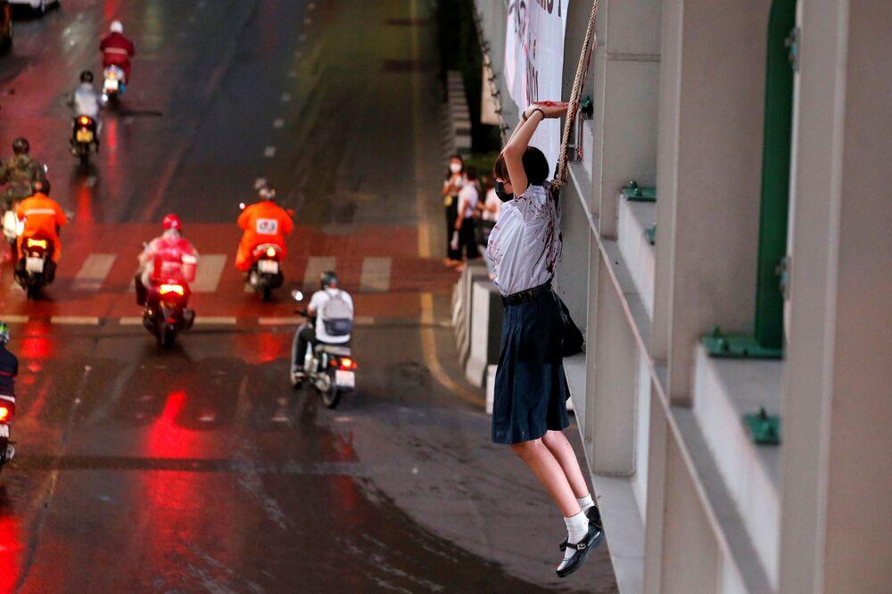 متظاهرة تلعب دور شخص شنق نفسه، خلال احتجاج على تعامل الحكومة التايلاندية مع جائحة كورونا (كوفيد-19) والمطالبة باستقالة رئيس الوزراء برايوت تشان أوتشا، في بانكوك، تايلاند، 6 سبتمبر 2021