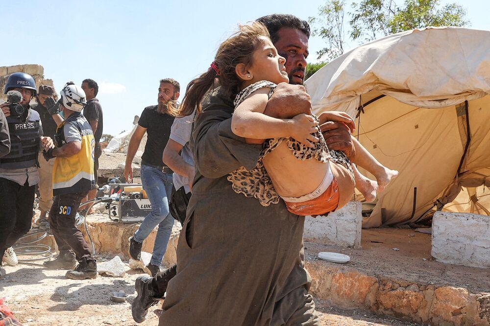 رجل يحمل فتاة أصيبت بجروح خلال قصف جوي على مخيم مؤقت للنازحين السوريين بالقرب من بلدة كفريا، شمال محافظة إدلب، سوريا 7 سبتمبر 2021