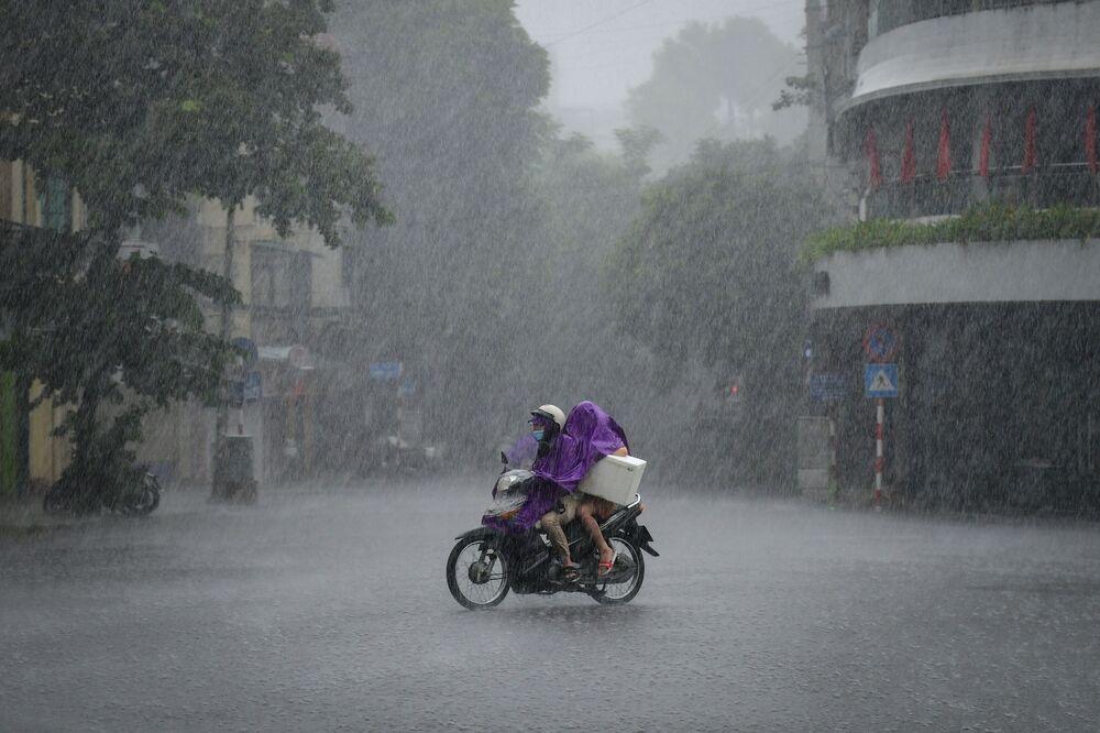 سائقي السيارات يركبون دراجة وسط هطول أمطار غزيرة في هانوي، فيتنام 8 سبتمبر 2021