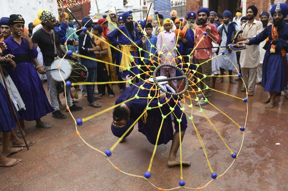 شاب من السيخ يؤدي فنون الدفاع عن النفس السيخية المعروفة باسم غاتكا '' بمناسبة الذكرى الـ 417 لتركيب غورو غرانث صاحيب، في المعبد الذهبي في أمريتسار، 7 سبتمبر 2021
