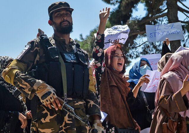 نساء أفغانيات يرددن شعارات بجانب أحد مسلحي حركة طالبان خلال مظاهرة مناهضة لباكستان بالقرب من السفارة الباكستانية في كابول، أفغانستان 7 سبتمبر 2021
