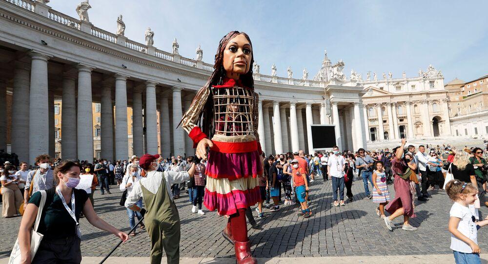 الصغيرة أمل، لعبة طولها 3.5 م، تمثل فتاة سورية، التي وصلت إلى الفاتيكان بعد رحلتها من التي انطلقت من تركيا إلى أوروبا، في إطار السير لـ 8000 كم من التوعية حول محنة اللاجئين الشباب، 10 سبتمبر 2021