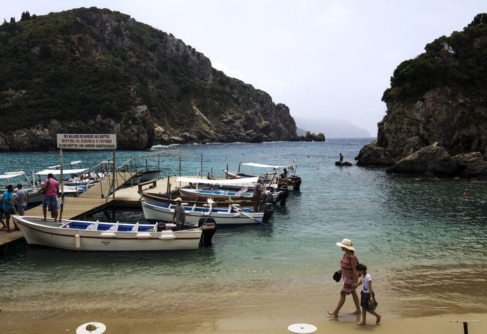 سياح على شاطئ البحر الأدرياتيكي في قرية باليوكاستريتسا على جزيرة كورفو، اليونان