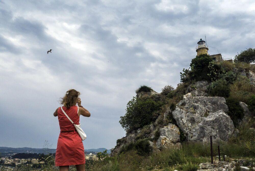 فتاة تلتقط صورة لمنارة في أعلى القلعة القديمة لمدينة كركيرا في جزيرة كورفو اليونانية