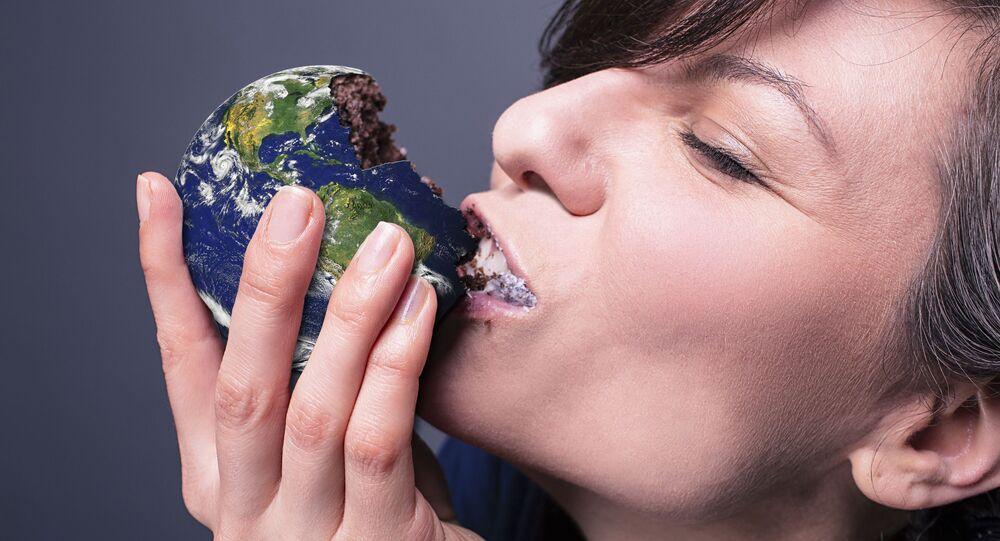 فتاة تتناول قطعة حلوى على شكل كرة أرضية