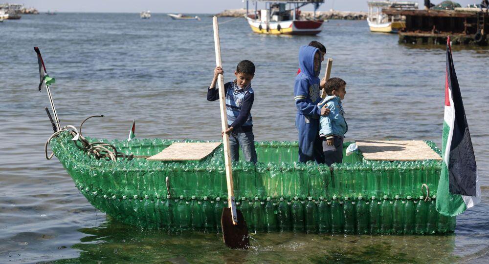 أطفال فلسطينيون على متن قارب مصنوع من الزجاجات البلاستيكية في ميناء مدينة غزة