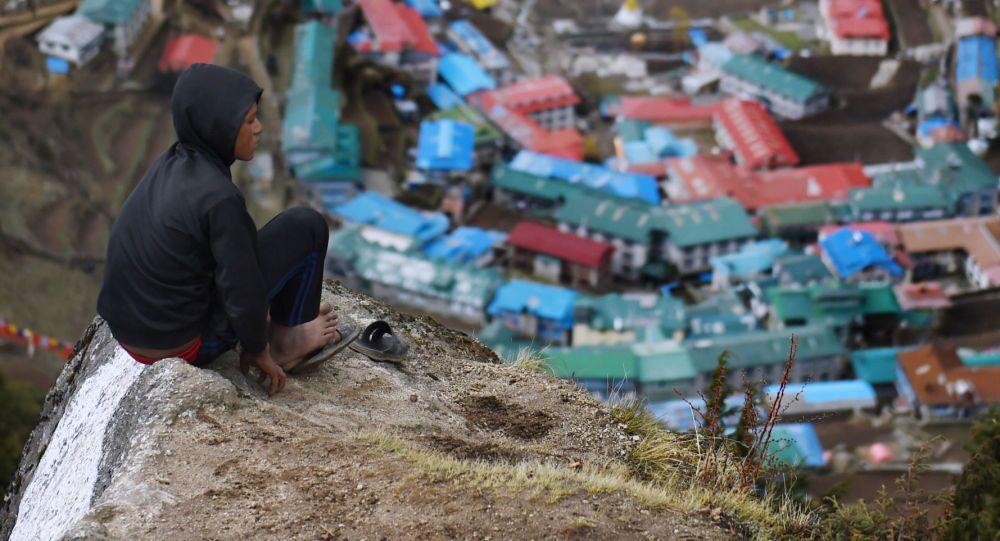 حمال نيبالي ميلان راي يبلغ من العمر 14 عاما يستريح على رأس قمة صخرية في الجزء العلوي من قرية بازار، التي تقع في الطريق إلى قمة إيفرست