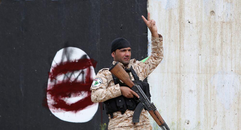 فرد من قوات الأمن العراقية يرفع إشارة النصر في تكريت