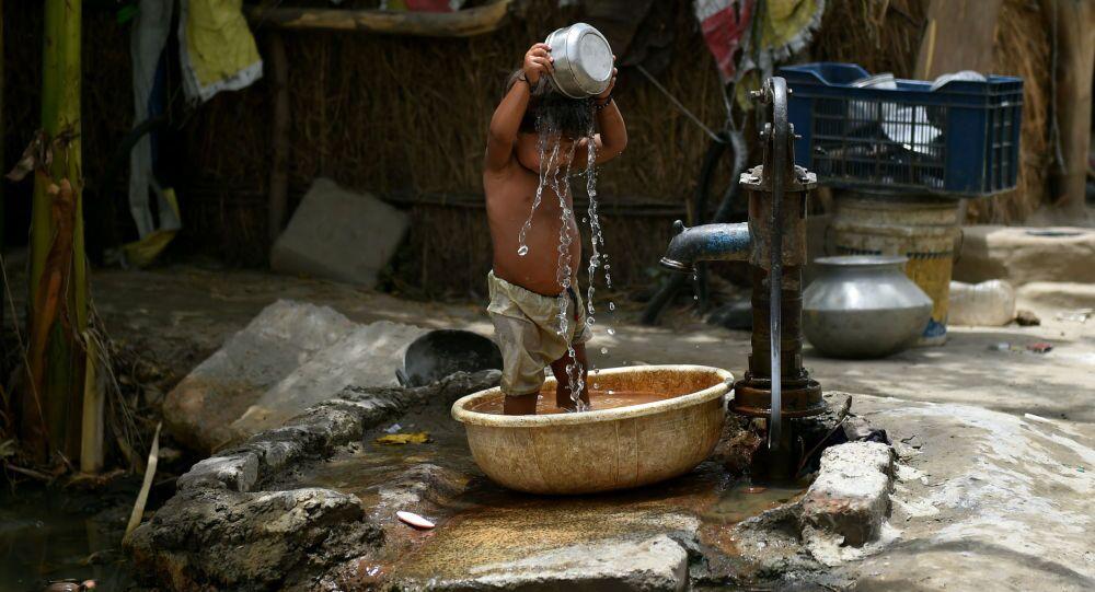 طفل هندي يصب على نفسه الماء هربا من الحر
