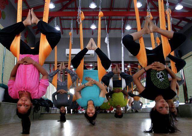 فتيات يمارسن تدريب ضد الجاذبية فى رياضة اليوجا فى مدينة أحمد أباد الهندية