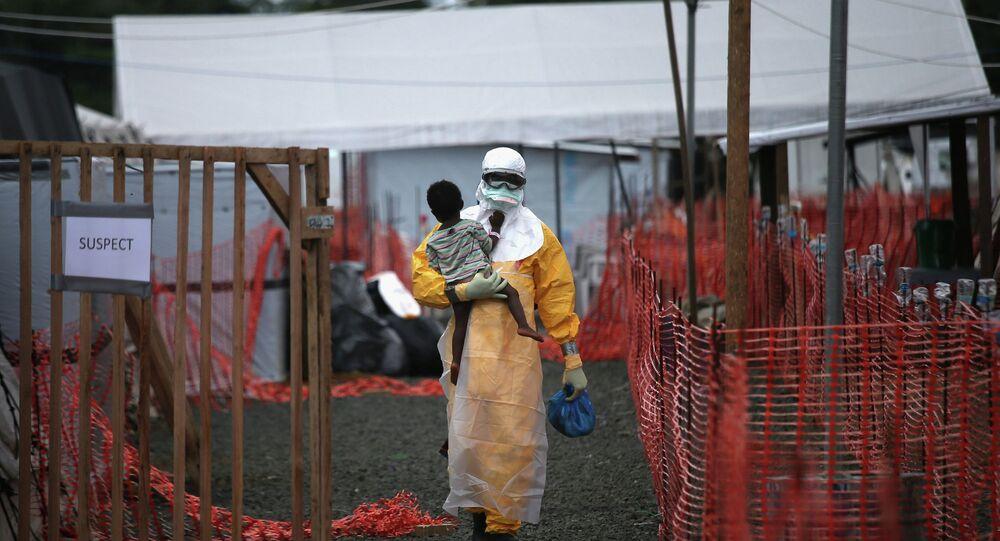 طبيب يحمل طفلا يشتبه بإصابته بفيروس إيبولا