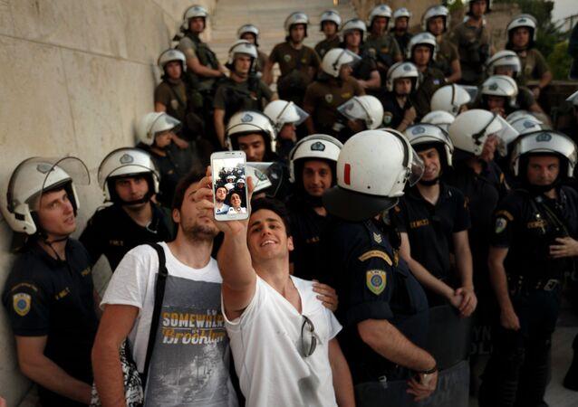 يونانيون يأخذون السليفى مع قوات الأمن خلال مسيرة إحتجاجية ضد الإتحاد الأوروبي أمام البرلمان اليوناني
