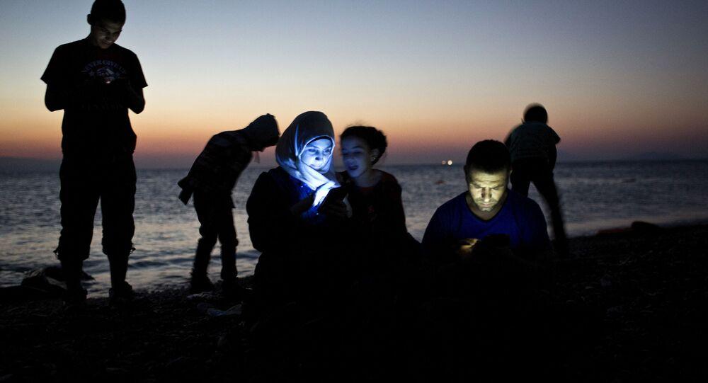 مهاجرين يتفقدون هواتفهم على اليابسة في جزيرة كوس اليونانية بعد رحلة طويلة في قوارب مطاطية