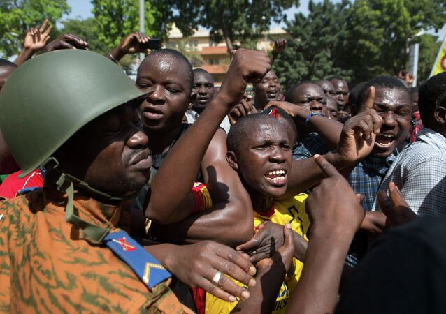 Anti-government protesters chant slogans in front of army headquarters in Ouagadougou, capital of Burkina Faso