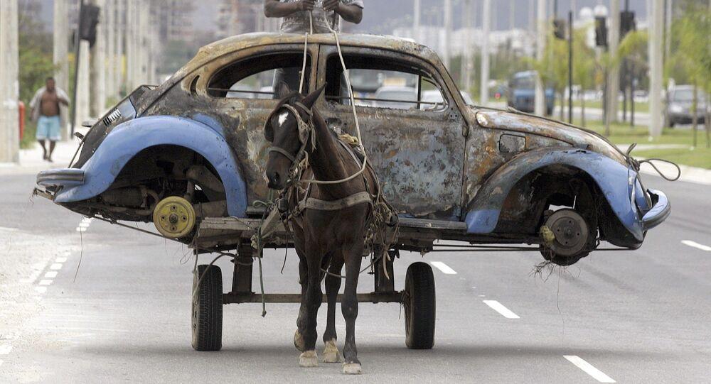 رجل البرازيلي ينقل على عربة يجرها حصان بقايا سيارة فولكس واغن بيتل اشتعلت فيها النيران وكان صاحبها تخلى عنها، ريو دي جانيرو، البرازيل،