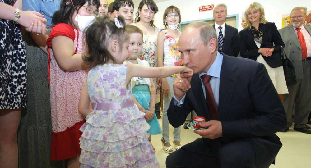 الرئيس بوتين يقبل يد طفلة صغيرة قامت بتقديم هدية له أثناء زيارته إلى مركز أمراض الدم، والمناعة والأورام