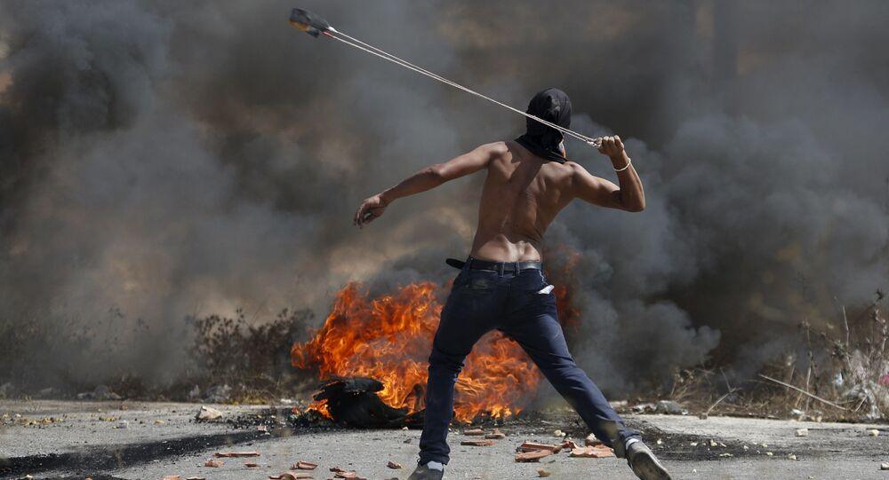 شاب فلسطيني يقذف الحجارة على قوات الاحتلال الإسرائيلي خلال الاشتباكات في بيت ايل