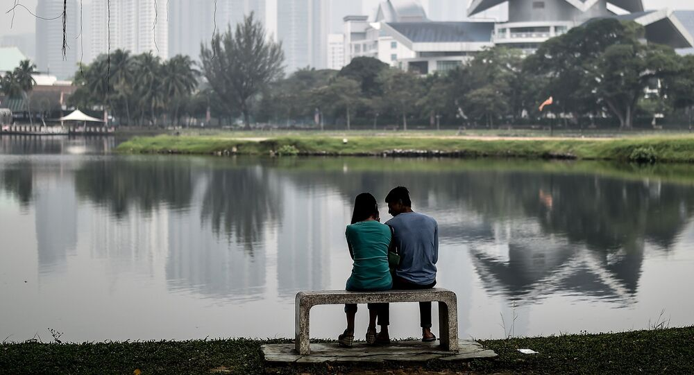 A Malaysian couple sit by a lake near the landmark Twin Towers (back R) on a hazy day in Kuala Lumpur
