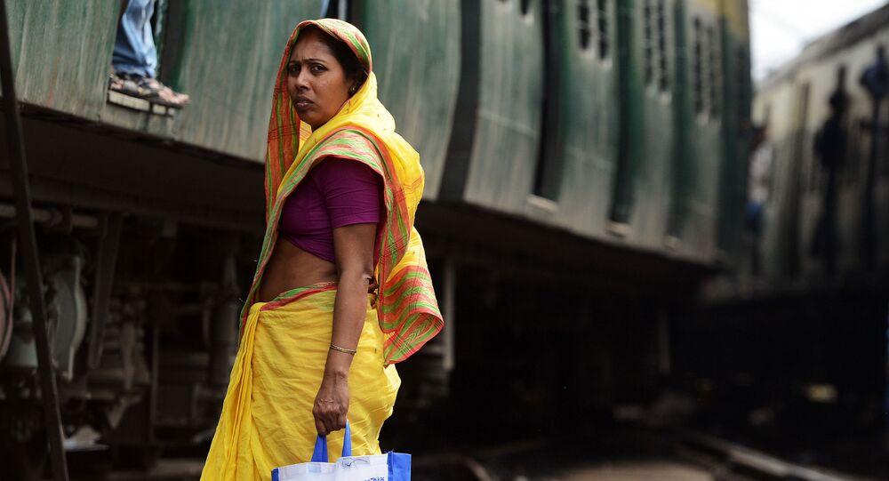 امرأة هندية تنتظر مرور قطار لكي تقطع السكة الحديدية بمحطة القطار في كالكوتا، 25 فبراير/ شباط 2015. وأعلنت وزارة السكك لحديدية، في نفس اليوم،  في الهند أنها ستوفر كافة محطات القطار بـ الانترنت اللاسلكي.