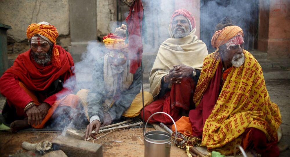 الهنديون المقدسون، أو رجال سادهو، يجلسون القرفصاء أمام النار في معبد باشوباتيني في كاذاماندو بنيبال، 6 مارس/ آذار 2016.