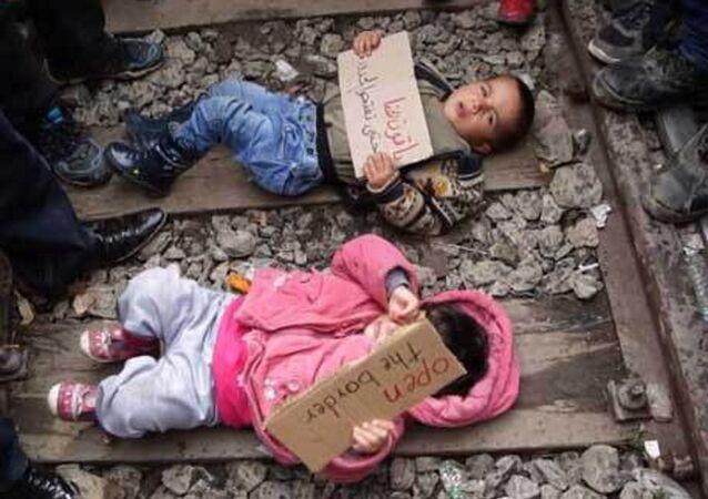 لاجئون يضعون أطفالهم على سكة القطار مع لافتات كتب عليها افتحوا الحدود