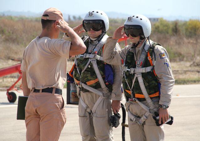طيارا القوات الجوية-الفضائية الروسية يحييان قائدهما في القاعدة الجوية السورية حميميم.