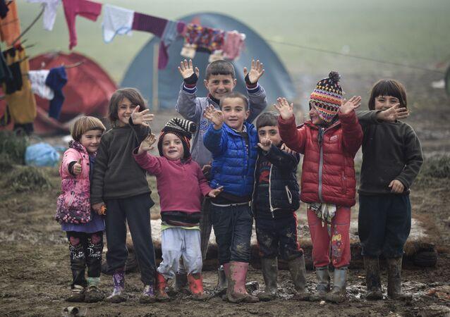 أطفال اللاجئين يلوحون بأيديهم الصغيرة للمصور، الحدود اليونانية، 18 مارس/ آذار 2016.