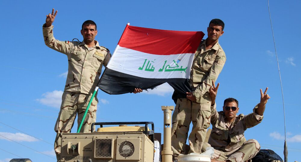 Iraqi government forces wave the national flag from their vehicles in the village of Mohammadi, a few miles north of Heet, in Iraq's western province of Anbar on March 18, 2016.