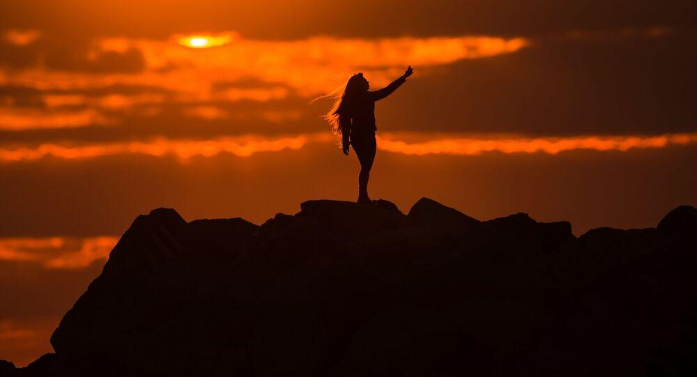 فتاة تلتقط صورة سيلفي لها على خلفية غروب الشمس في أدلير