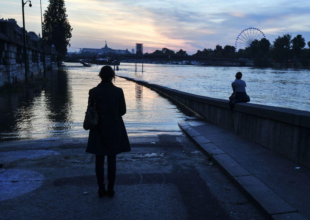 الفياضانت في فرنسا - مارة فرنسيون على ضفة نهر الساين في ضواحي متحف أورسي في باريس.
