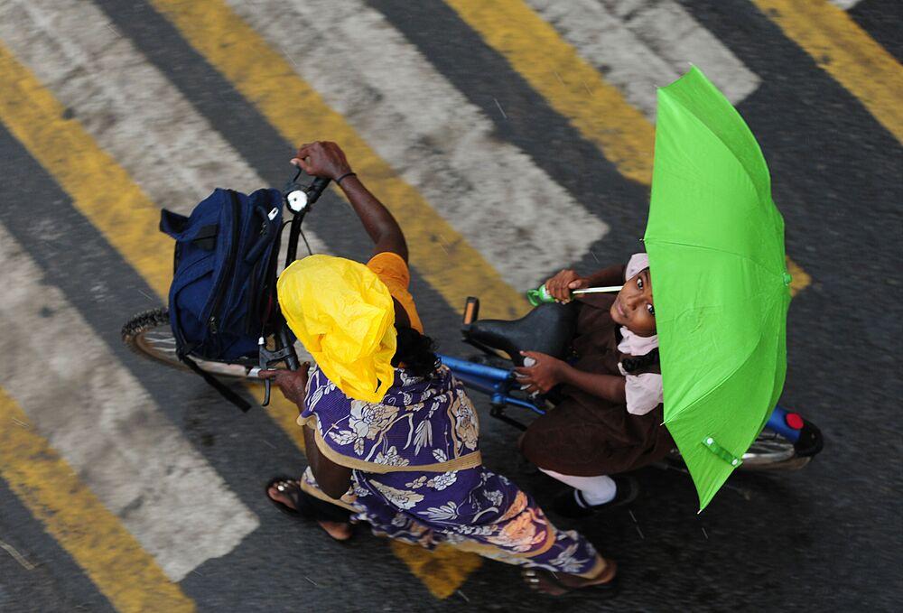 فتاة هندية تحمل شمسية تركب دراجة هوائية تقط الطريق في تشيناي، 8 يونيو/ حزيران 2016.