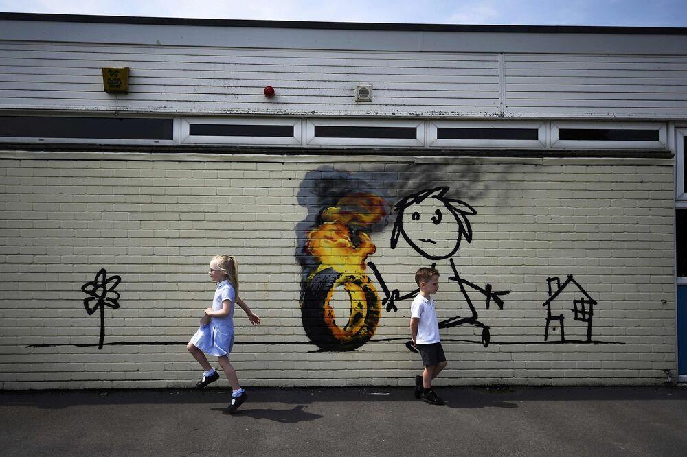 أطفال يلعبون على خلفية جدارية للفنان بانكسي (Banksy) على جدار لمدرسة الابتدائية في بريستول، بريطانيا 6 يونيو/ حزيران 2016.