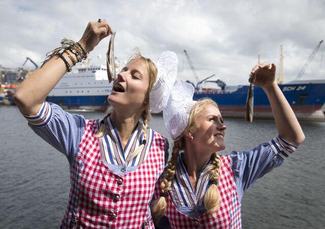 فتاتان ترتديان زياً تقليدياً هولندياً وتتصوران مع سمك الفسيخ نيو هارينغ في ميناء سخيفينينغن، 14 يونيو/ حزيران 2016. وذلك من أجل مزاد خيري بقيمة 90000.