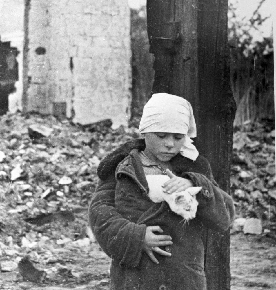 فتاة وقطة أما منزل مدمر.