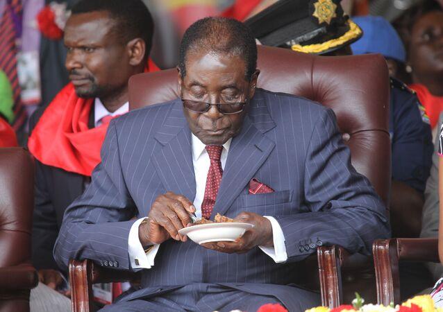 رئيس الزيمبابوي روبيرت موغابي يأكل قطعة الكيك خلال الاحتفال بعيد ميلاده الـ 92، عام 2016