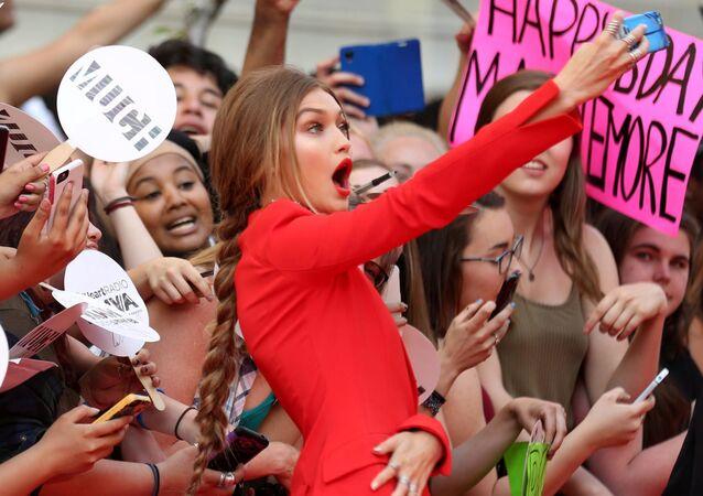 عارضة الأزياء الأمريكية جيجي حديد تلتقط صورة سيلفي على خلفية مشجعاتها قبيل احتفال توزيع جوائز iHeartRadio Much Music Video Awards  في تورونتو بكندا، 19 يونيو/ حزيران 2016