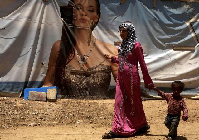 لاجئة سورية من حلب وطفلها على خلفية خيمة عليها رسم إعلاني، مخيم اللاجئين في لبنان 20 يونيو/ حزيران 2016