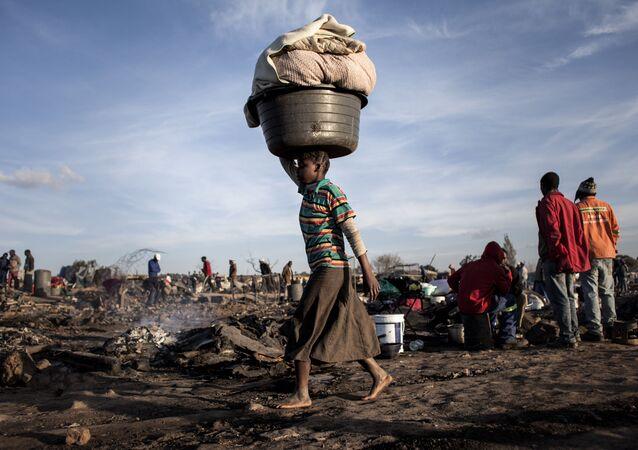 امرأة تحمل على رأسها كل ما تبقى من بعد حريق في بيتوريا، جمهورية جنوب أفريقيا 3 يوليو\ تموز 2016