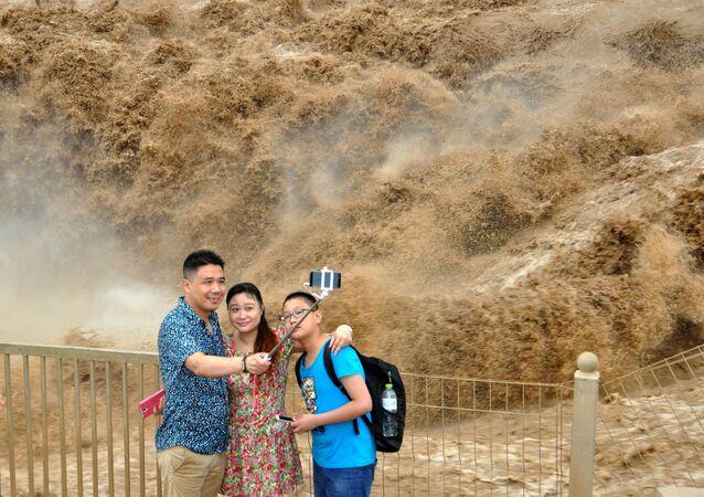 أشخاص يلتقطون صور سيلفي على خلفية شلال خوكاو، وهو أكبر شلال يطل على نهر خوانخي، الصين 10 يوليو/ تموز 2016
