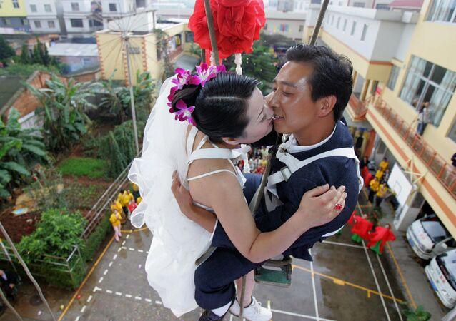 الاحتفال بالزواج (معلقين ما بين طوابق عمارة)على بعد عدة أمتار من سطح الأرض، الصين.