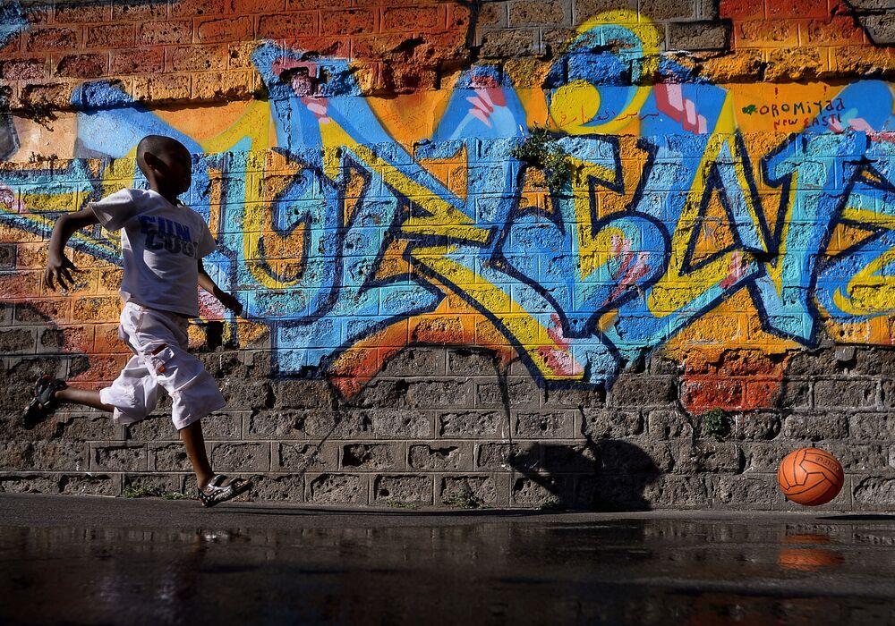 طفل لاجئ يجري خلف الكرة على خلفية جدارية في شارع فيا كوبا بالقرب من مركز لإيواء المهاجرين في روما، 8 أغسطس/ آب 2016