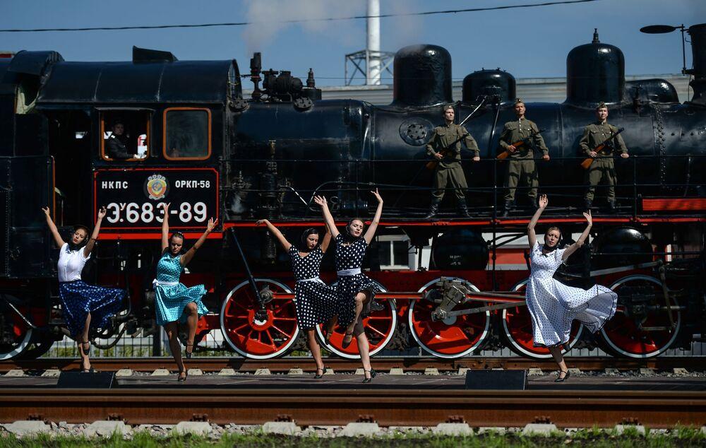 أعضاء حفل مسرحي على خلفية القاطرات البخارية على شرف عيد عمال السكك الحديدية في ضواحي موسكو.