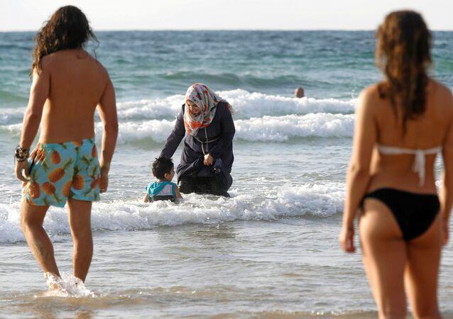 امرأة محجبة وطفلها في البحر على شاطئ تل-أبيب، 22 أغسطس/ آب 2016