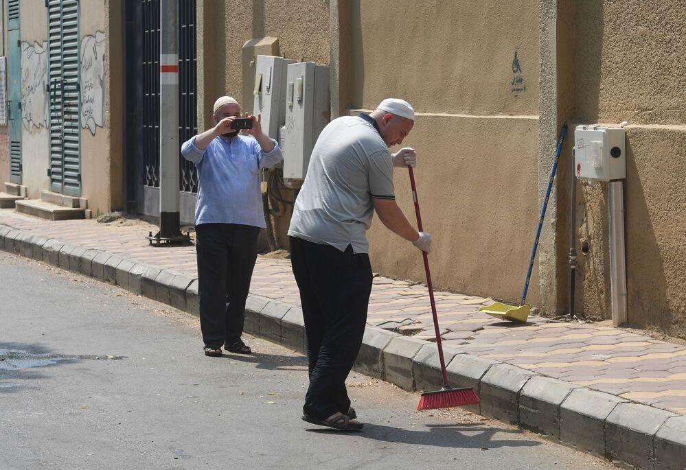 الحجاج الروس في مكة ينظفون الشارع من القمامة