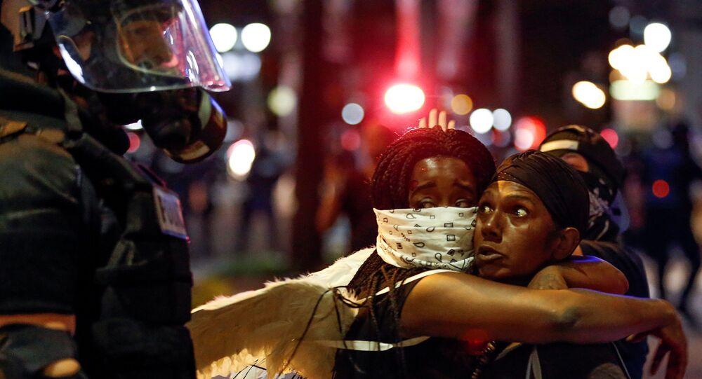 عناق امرأتان أمام الشرطة خلال احتجاجات في مدينة شارلوت الأمريكية